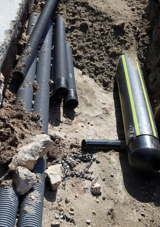 powerhouse: corrugated pipes and a big gas pipeline inside the excavation in road construction