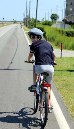 ten year old: ten year old Child goes to bike with grey helmet Stock Photo