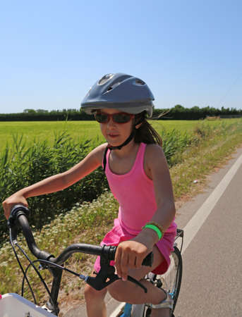 eight year old: eight year old girl goes to bike with protective helmet