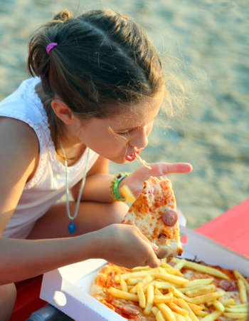 beautiful Little Girl eats a slice of pizza on the beach at sunset in summer