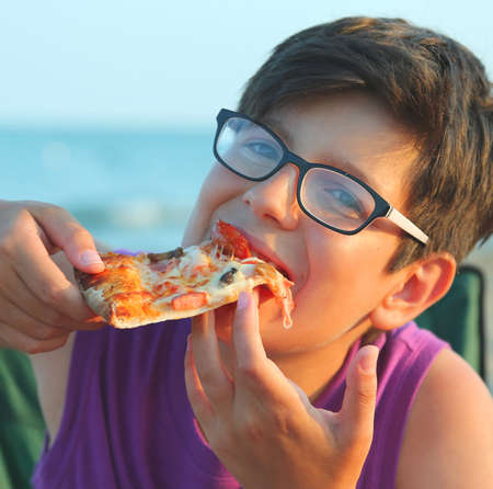 eating pizza: Young boy eats a slice of pizza on the beach at sunset in summer