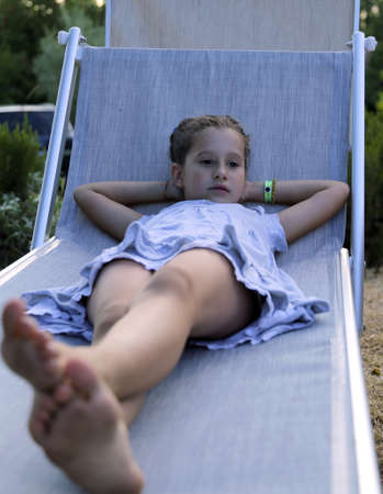 little girl barefoot: beautiful little girl resting on the deck at sunset