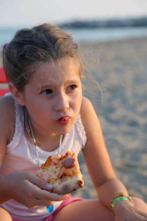 beach babe: beautiful babe eats a slice of pizza on the beach at sunset in summer Stock Photo