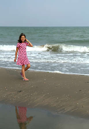 beach babe: beautiful Little Girl with pink dress with small black hearts of the beach in summer Stock Photo