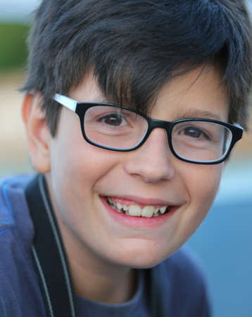 visually: Portrait of smiling Caucasian Young boy with glasses