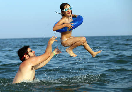 seawater: muscled Daddy plays with her daughter by making her do high dives in seawater