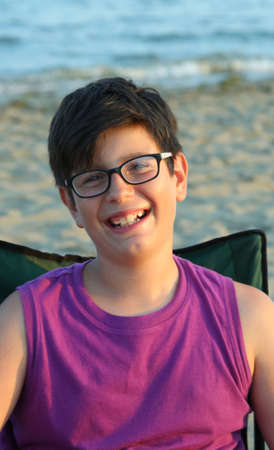 nearsighted: Portrait of smiling Caucasian boy with glasses on the beach