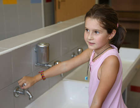 smiling little girl is washing her hands in the sink in the bathroom of the school Stock Photo