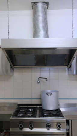 industrial kitchen: large industrial kitchen cooker with aluminum pot and the giant smoke ventilation hood