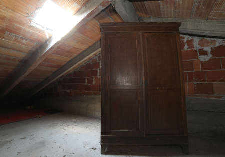 attic: antique wooden wardrobe in the dusty attic
