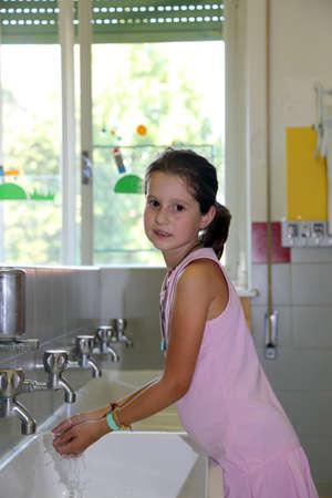 pretty little girl: pretty little girl washing hands in the ceramic sink in the bathroom  of school