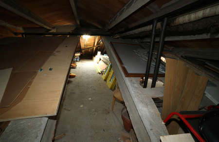 attic: Junk and old furniture in large attic under the roof of the school Stock Photo