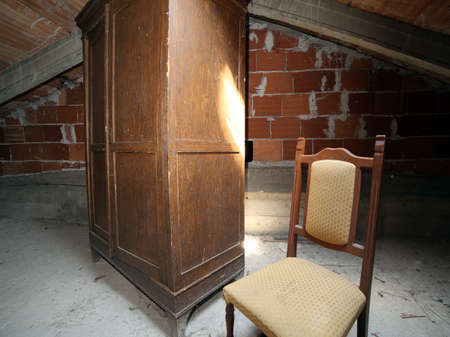 antique chair: old wooden wardrobe and an antique chair in the dusty attic