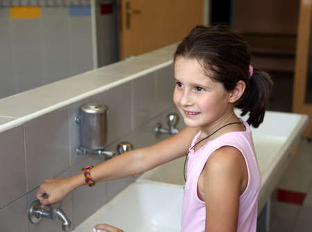 toilet sink: little girl is washing her hands in the sink in the bathroom of the school
