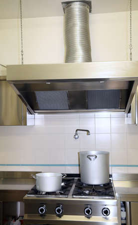 extractor hood: large fume Extractor hood in the industrial kitchen with pots on the stove top