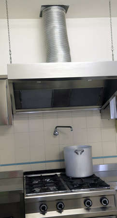 extractor hood: large industrial kitchen cooker with aluminum pot and the gigantic  smoke ventilation hood