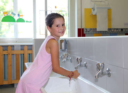 pretty little girl washing hands in the ceramic sink in the bathroom  of school