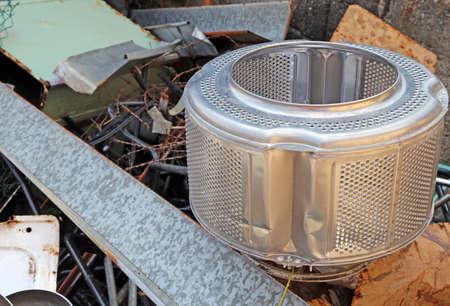 reciclable: cesta de lavadora y piezas oxidadas de hierro en el vertido de material reciclable