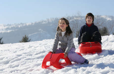 to go sledding: Winter holidays playing with red sled on the snow in the mountains in winter