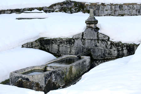 stone cold: stone fountain with freezing cold water in winter Stock Photo