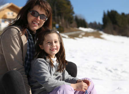 sledging people: mom and girl in the mountain on sledge