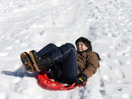 sledging: Boy plays with sledging in winter on the white snow in the mountains Stock Photo