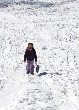 sledging: Little Girl plays with sledging in winter on the white snow in the mountains
