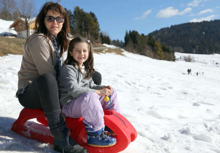 sledging people: mom and little girl in the mountain on sledge Stock Photo