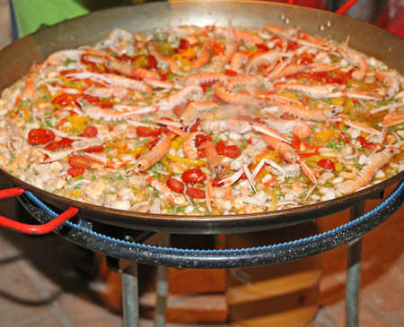lobster pot: Spanish paella with prawns and rice cooked on a large pot in the restaurant Stock Photo