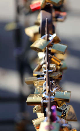 hung: many large padlocks hung on the side of the bridge lovers as a sign of love forever