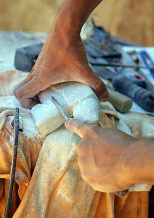 sculpting: hand of an expert craftsman and stone sculpting