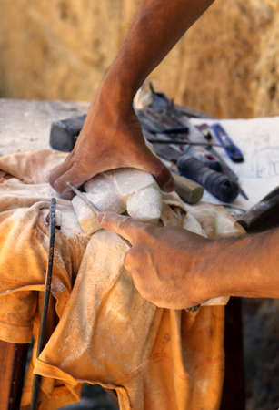 sculpting: expert craftsman hand while sculpting Alabaster stone Stock Photo