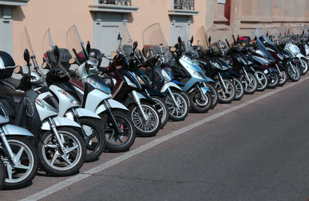 mopeds: many mopeds scooters and motorcycles parked along the busy street
