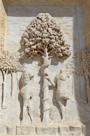 adam and eve: statues of Adam and Eve with Apple tree in the facade of Italian Abbey Called Certsosa di Pavia