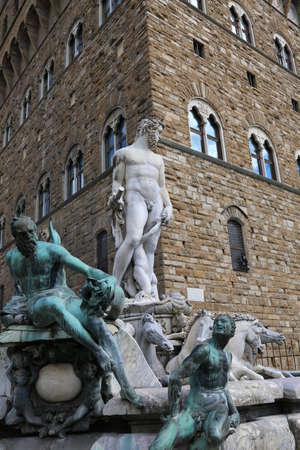 signoria square: Big White statue of Neptune in the ancient fountain in Florence and Palazzo Vecchio in background Editorial