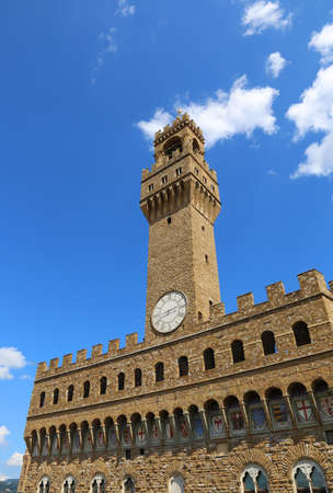 signoria square: Old Palace called Palazzo Vecchio and clock tower with blue sky in Signoria square in Florence Italy Editorial