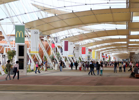 main street: Milan, Italy - 8th September, 2015. International Exposition EXPO MILANO 2015. Main street called Decumano with flags and people Editorial