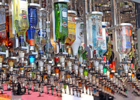 automatically: Milan, Italy - 8th September, 2015. EXPO MILANO 2015. Many bottles of spirits in a futuristic automated bar for the preparation of customized drinks automatically Editorial
