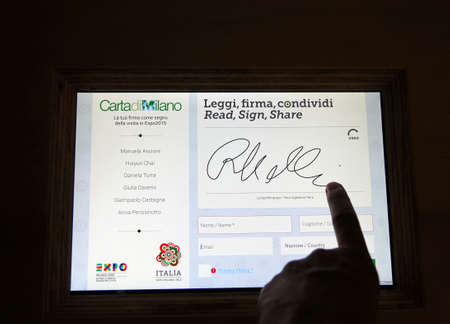 signer: Milan, Italy - 8th September, 2015. EXPO MILANO 2015. Electronic signature of Milan Charter. The document is a commitment to the efficient use of land resources  and for the protection of climate.
