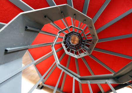 red carpet background: long spiral staircase with red carpet in a modern building Stock Photo