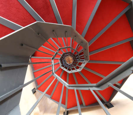 long spiral staircase with red carpet in a modern building Stock Photo