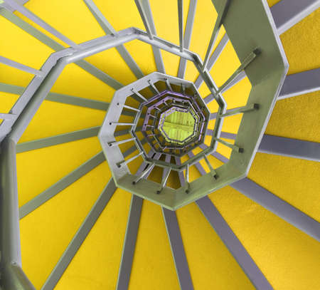spiral staircase: long spiral staircase with yellow carpet in a modern building Stock Photo