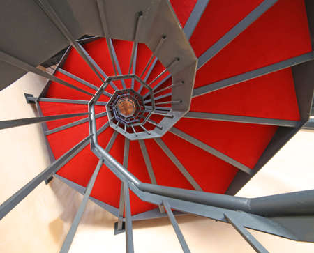 spiral staircase: spiral staircase with red carpet in a modern building Stock Photo