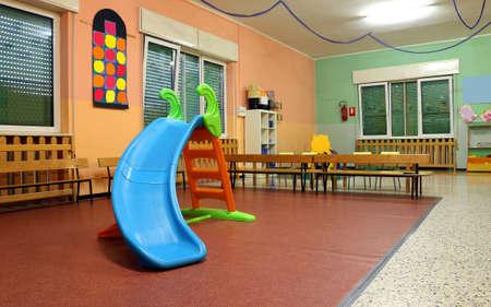 Grande salle de jeux dans une pépinière avec la glissière en plastique pour les enfants