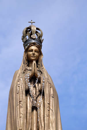 ancient statue of our Lady with clasped hands Stock Photo