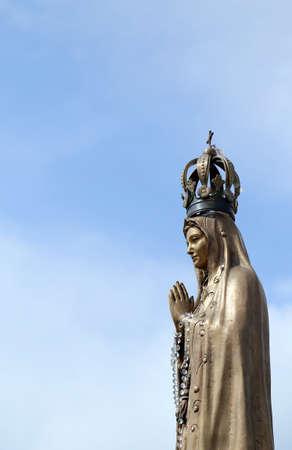 virgen maria: antigua estatua de la Virgen con las manos juntas y la preciosa corona Foto de archivo