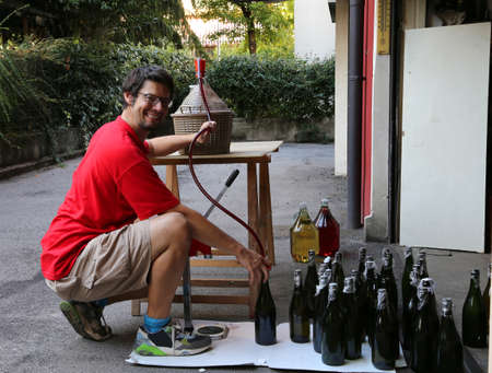 bottling: young man smiling while bottling the wine at home in glass bottles