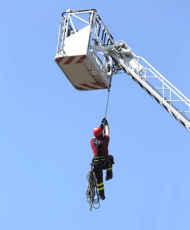 rappel: fireman down with the rope in the building during a fire alarm in the firehouse