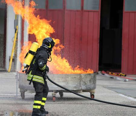 bombera: bomberos con botellas de oxígeno fuera del fuego durante un ejercicio de entrenamiento en el parque de bomberos