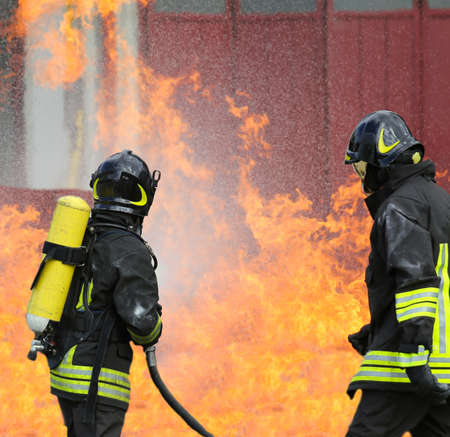 bombero: bomberos con botellas de ox�geno fuera del fuego durante un ejercicio de entrenamiento en el parque de bomberos